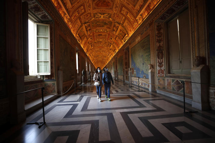 Visitors wearing masks to prevent the spread of coronavirus walks inside the Vatican Museum after it reopened, in Rome, Monday, May 3, 2021. The Vatican Museums reopened Monday to visitors after a shutdown following COVID-19 containment measures. (AP Photo/Alessandra Tarantino)