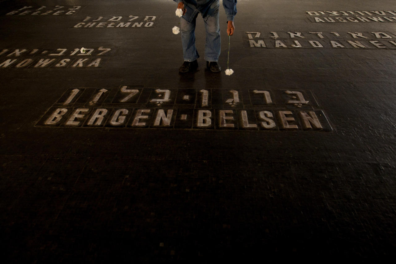 A Holocaust survivor lays flowers next to the names of concentration camps during the annual ceremony on Holocaust Remembrance Day at the Yad Vashem memorial in Jerusalem, Thursday, April 19, 2012. Israel is marking its annual remembrance day for the six million Jews killed by the Nazis in World War II. (AP Photo/Ariel Schalit)