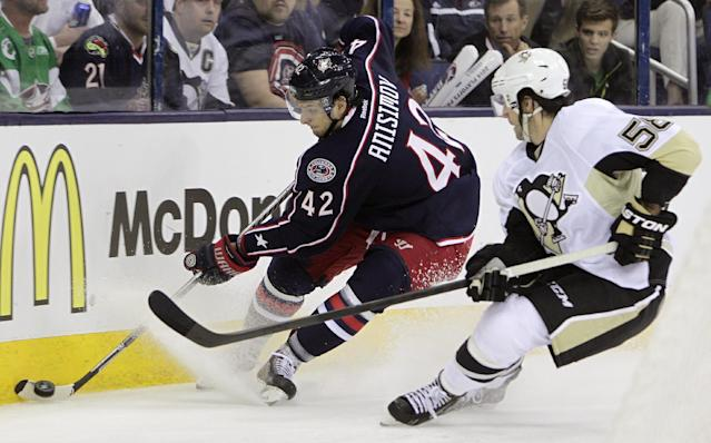 Columbus Blue Jackets' Artem Anisimov, left, of Russia, tries to clear the puck as Pittsburgh Penguins' Kris Letang defends during the second period of a first-round NHL playoff hockey game Monday, April 21, 2014, in Columbus, Ohio. (AP Photo/Jay LaPrete)