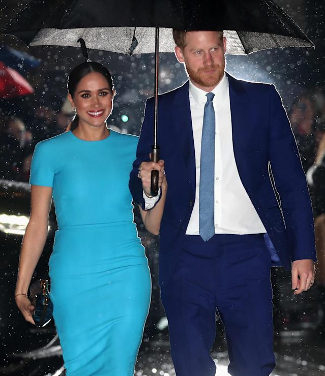 The couple sheltered under an umbrella as they arrived. (Getty Images)