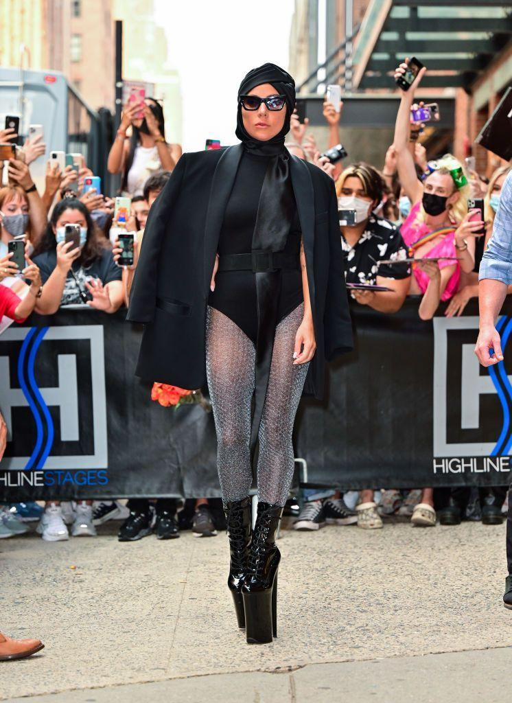 """<p>Lady Gaga continued her vertiginous fashion tour of the city by pairing a black turban with a leotard. The actor added an oversized black blazer to the look, and accessorised with black sunglasses, glittery tights and those super high heels. </p><p><a class=""""link rapid-noclick-resp"""" href=""""https://www.dollskill.com/uk/pleaser-players-club-adore-vinyl-heels.html"""" rel=""""nofollow noopener"""" target=""""_blank"""" data-ylk=""""slk:SHOP PLEASER BOOTS NOW"""">SHOP PLEASER BOOTS NOW</a></p>"""