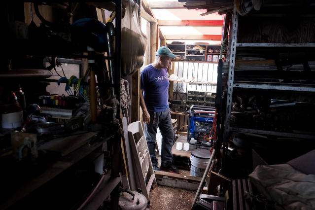 Jesse Vazquez in his home in Bayamon, Puerto Rico, with the generator that his children brought with them from New York. (Photo: Jose R. Madera for Yahoo News)