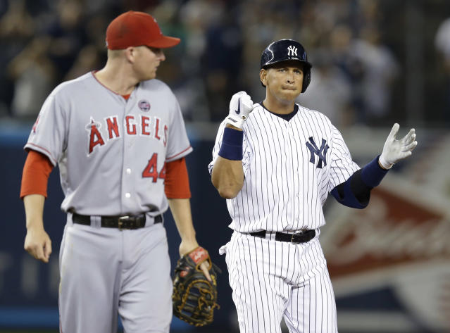 Los Angeles Angels first baseman Mark Trumbo (44) looks over his shoulder as New York Yankees' Alex Rodriguez reacts after hitting a sixth-inning, two-run double in a baseball game, Tuesday, Aug. 13, 2013, in New York. (AP Photo/Kathy Willens)
