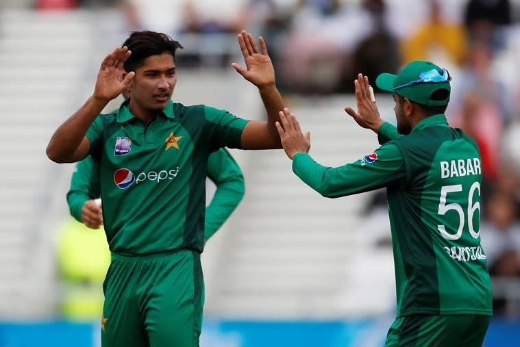 Pakistan's Mohammad Hasnain celebrates with Babar Azam after taking the wicket of England's Joe Root