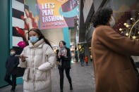 People wearing face masks to protect against the coronavirus walk at an outdoor shopping area in Beijing, Saturday, Nov. 28, 2020. (AP Photo/Mark Schiefelbein)