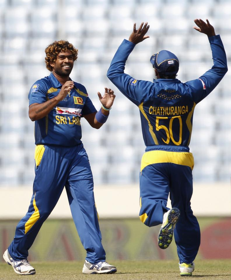 Sri Lanka's Chaturanga de Silva congratulates teammate Lasith Malinga (L) as he dismissed Pakistan's Sharjeel Khan (not pictured) successfully during their 2014 Asia Cup final match in Dhaka March 8, 2014. REUTERS/Andrew Biraj (BANGLADESH - Tags: SPORT CRICKET)
