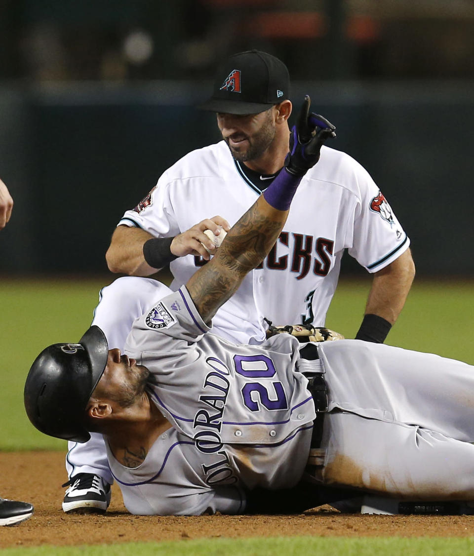 Colorado Rockies' Ian Desmond (20) and Arizona Diamondbacks second baseman Daniel Descalso talk after Desmond tried to extend a single into a double in the fifth inning during a baseball game, Friday, Sept. 21, 2018, in Phoenix. (AP Photo/Rick Scuteri)