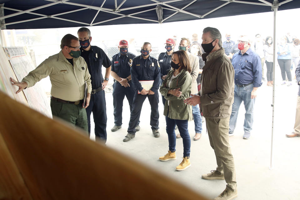 Democratic vice presidential candidate Sen. Kamala Harris, D-Calif., and California Gov. Gavin Newsom are briefed on the damage during the Creek Fire at Pine Ridge Elementary, Tuesday, Sept. 15, 2020 in Auberry, Calif. (AP Photo/Gary Kazanjian)