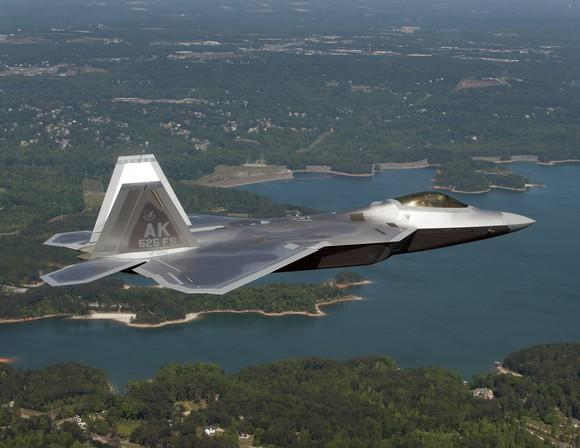 An F-22 Raptor flying over land and water.