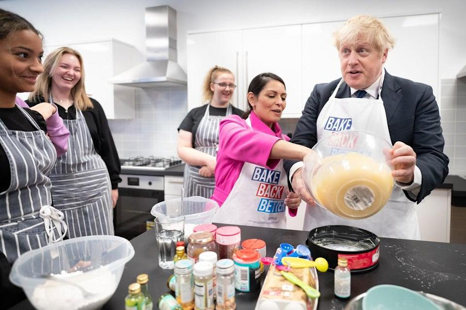 Mr Johnson was aided by Ms Patel as he made the cake (Stefan Rousseau/PA) (PA Wire)