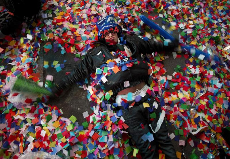 A reveler makes angels in the confetti on the ground during New Year's Eve celebrations in Times Square in New York