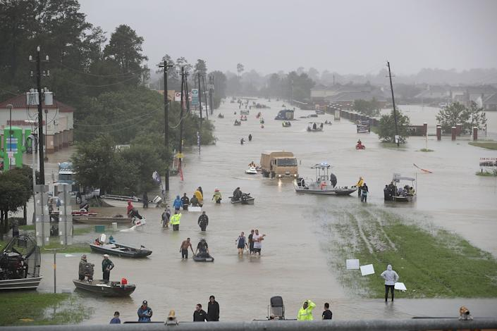 Groups of people walk down a flooded street in Houston.