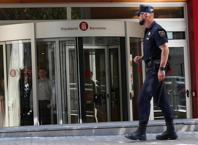 A Spanish national police officer walks by the entrance of one of the Catalan public offices which were raided as police investigators raided several Catalan public institutions in search of evidence of alleged rerouting of public funds to organisations associated with a pro-independence bid, according to Spanish media, in Barcelona, Spain, May 24, 2018. REUTERS/Albert Gea