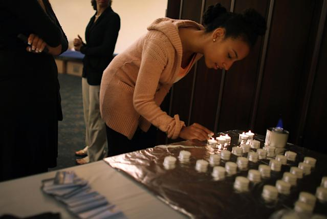 MIAMI BEACH, FL - MARCH 25: Addisa Goldman lights candles during a community Passover Seder at Beth Israel synagogue on March 25, 2013 in Miami Beach, Florida. The community Passover Seder that served around 150 people has been held for the past 30 years and is welcome to anyone in the community that wants to commemorate the emancipation of the Israelites from slavery in ancient Egypt. (Photo by Joe Raedle/Getty Images)