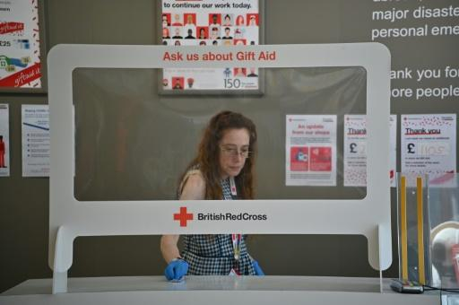 An employee cleans around the till protected by a 'sneeze screen' as a measure against the spread of COVID-19 at a British Red Cross charity shop in London