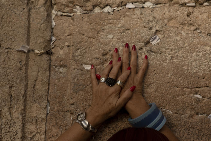 A woman prays at the Western Wall, the holiest site where Jews can pray, in the shadow of a wooden pedestrian bridge connecting the wall to the Al Aqsa Mosque compound, in Jerusalem's Old City, Tuesday, July 20, 2021. Experts say the rickety bridge that allows access to the Holy Land's most sensitive religious site is at imminent risk of collapse. But the shrine's delicate position at the epicenter of the Israeli-Palestinian conflict prevents it from being repaired -- raising fears of another disaster just months after 45 people were killed in a stampede at an ultra-Orthodox Jewish shrine where organizers had also ignored years of safety warnings. (AP Photo/Maya Alleruzzo)