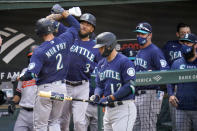 Seattle Mariners' Tom Murphy (2) is greeted near the dugout by J.P. Crawford (3) after hitting a solo home run off Baltimore Orioles starting pitcher John Means during the second inning of the first game of a baseball doubleheader, Tuesday, April 13, 2021, in Baltimore. (AP Photo/Julio Cortez)