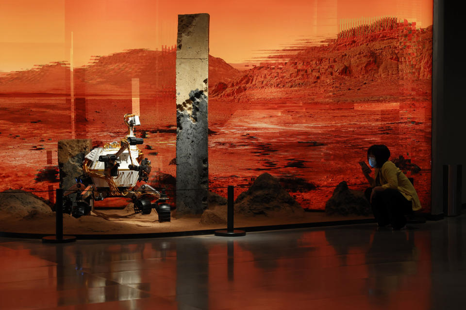 A woman wearing a mask talks on her phone near an exhibition depicting a rover in Mars in Beijing on Friday, May 14, 2021. China says its Mars probe and accompanying rover are to land on the red planet sometime between early Saturday morning and Wednesday Beijing time. (AP Photo/Ng Han Guan)
