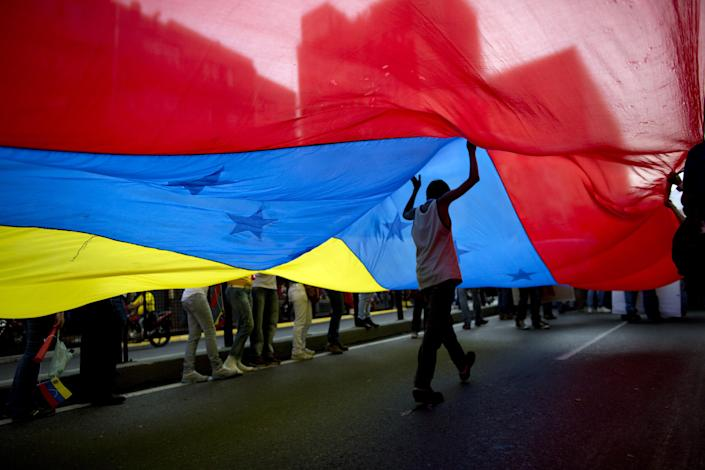 A youth walks under a large Venezuelan flag during a rally organized by workers of the National Telecommunications Company or CANTV to show support for the government in Caracas, Venezuela, Tuesday, Feb. 25, 2014. (AP Photo/Rodrigo Abd)