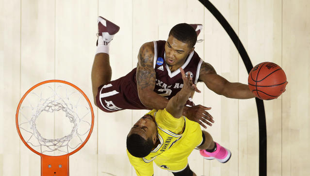Texas A&M guard TJ Starks, top, shoots against Michigan guard Jaaron Simmons during the first half of an NCAA men's college basketball tournament regional semifinal Thursday, March 22, 2018, in Los Angeles. (AP Photo/Alex Gallardo)