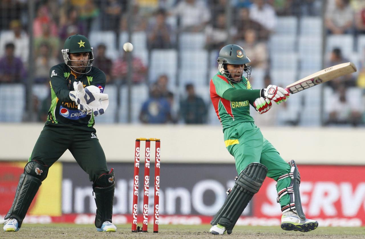 Bangladesh's Mushfiqur Rahim (R) plays a ball as Pakistan's wicketkeeper Umar Akmal tries to catch during their one-day international (ODI) cricket match in Asia Cup 2014 in Dhaka March 4, 2014. REUTERS/Andrew Biraj (BANGLADESH - Tags: SPORT CRICKET)