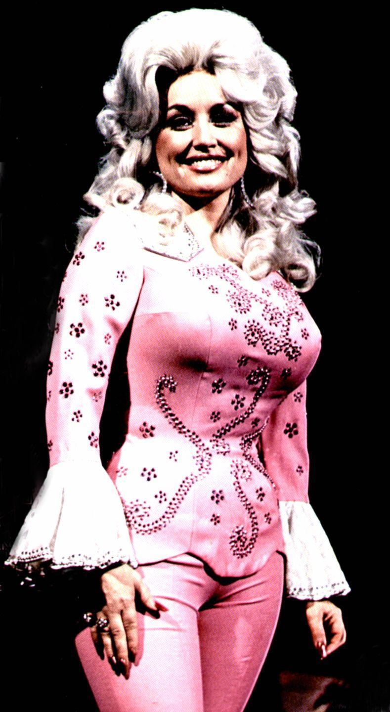 <p>Dolly Parton was rocking the pantsuit long before it was cool, and one of her first takes on the ensemble is classic Dolly: bell sleeves, floral embellishments, and Barbie pink with a pair of oversize hoop earrings..</p>