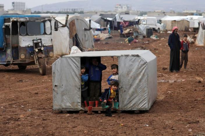 Internally displaced children look out from a tent at a makeshift camp in Azaz
