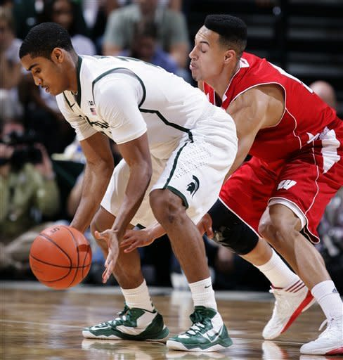 Wisconsin's Ryan Evans, right, reaches in on Michigan State's Gary Harris during the first half of an NCAA college basketball game, Thursday, March 7, 2013, in East Lansing, Mich. (AP Photo/Al Goldis)