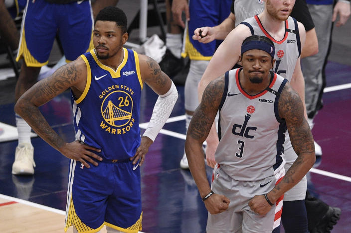 Washington Wizards guard Bradley Beal (3) reacts next to Golden State Warriors forward Kent Bazemore (26) during the second half of an NBA basketball game, Wednesday, April 21, 2021, in Washington. The Wizards won 118-114. (AP Photo/Nick Wass)