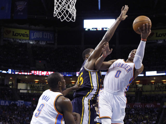 Oklahoma City Thunder guard Russell Westbrook (0) shoots in front of Utah Jazz forward Derrick Favors (15) and teammate Serge Ibaka (9) in the third quarter of an NBA basketball game in Oklahoma City, Sunday, March 30, 2014. Oklahoma City won 116-96. (AP Photo/Sue Ogrocki)