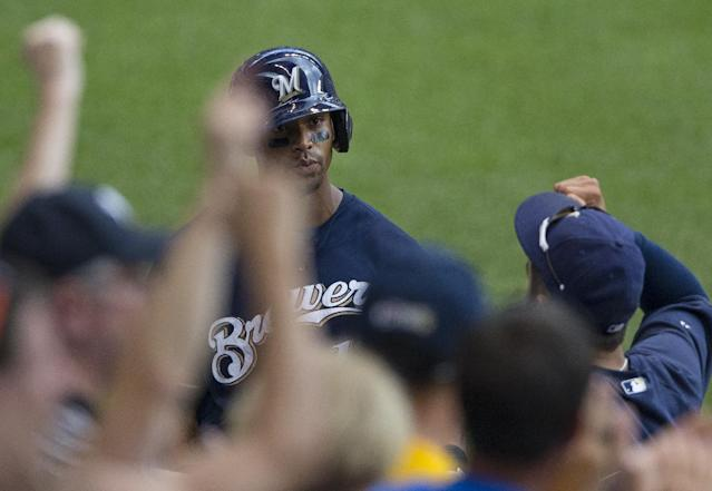 Milwaukee Brewers' Khris Davis is cheered on by fans and teammates after his solo home run against the St. Louis Cardinals during the fifth inning of a baseball game Sunday, July 13, 2014, in Milwaukee. (AP Photo/Tom Lynn)