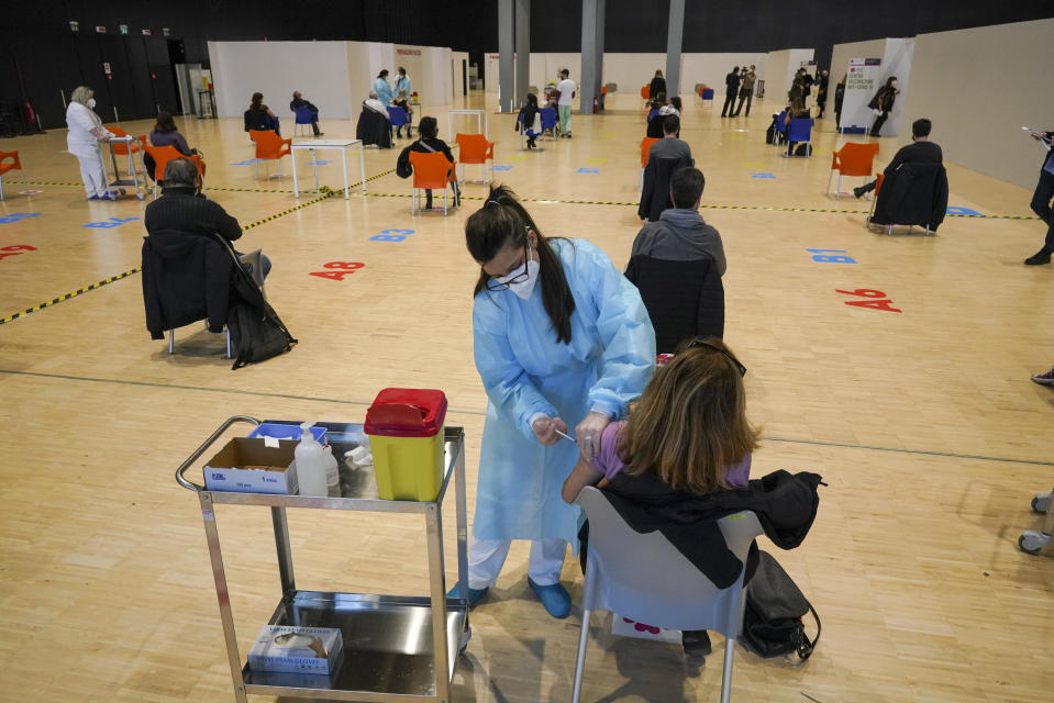 """Health workers administer doses of the AstraZeneca vaccine against COVID-19 inside the convention center known as """"La Nuvola"""", The Cloud, in Rome, Wednesday, March 10, 2021. The visually extraordinary complex designed by famed architect Massimiliano Fuksas has been transformed into a temporary vaccination center. (AP Photo/Andrew Medichini)"""