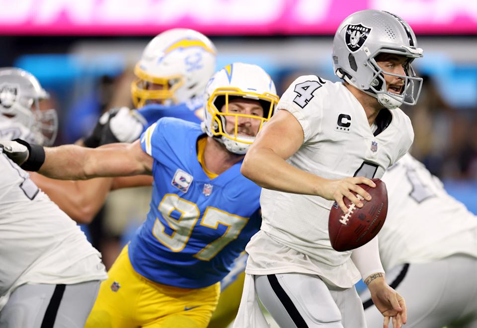 Derek Carr #4 of the Las Vegas Raiders scrambles away from Joey Bosa #97 of the Los Angeles Chargers during a 28-14 loss to the Chargers at SoFi Stadium on October 04, 2021 in Inglewood, California. (Photo by Harry How/Getty Images)