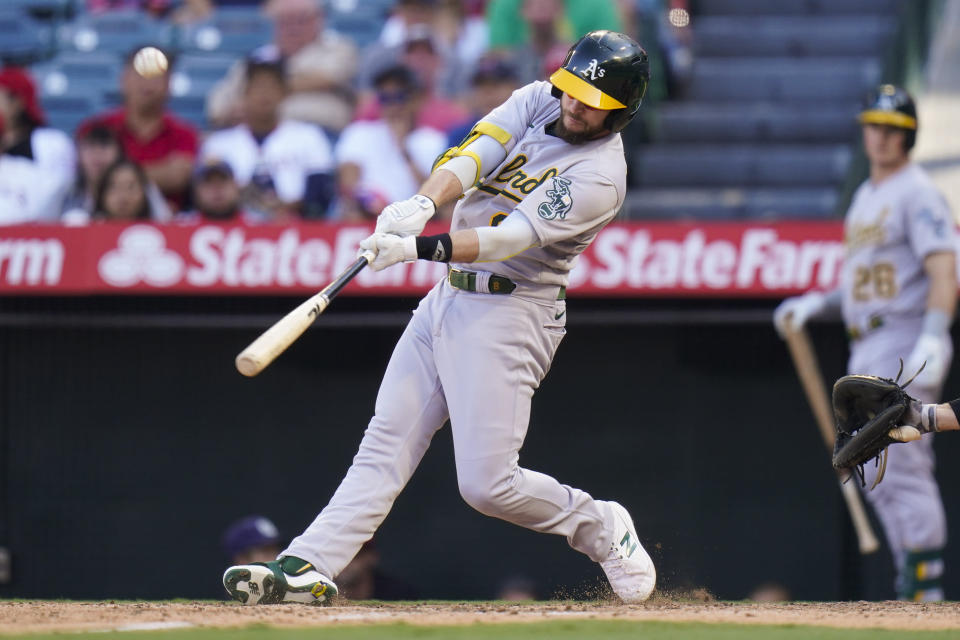 Oakland Athletics' Jed Lowrie hits a sacrifice fly to bring in Matt Olson to score during the 10th inning of a baseball game against the Los Angeles Angels, Sunday, Sept. 19, 2021, in Anaheim, Calif. (AP Photo/Jae C. Hong)