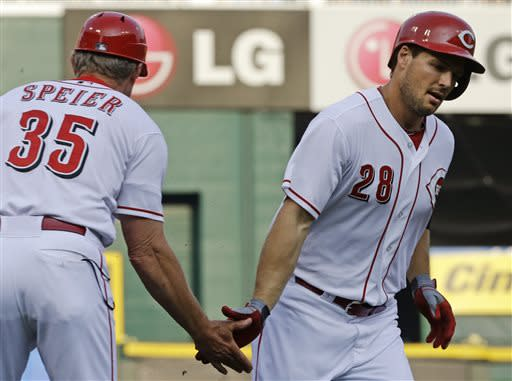 Cincinnati Reds' Chris Heisey (28) is congratulated by third base coach Chris Speier (35) after Heisey hit a solo home run off Pittsburgh Pirates starting pitcher Francisco Liriano in the first inning of a baseball game, Friday, July 19, 2013, in Cincinnati. (AP Photo/Al Behrman)