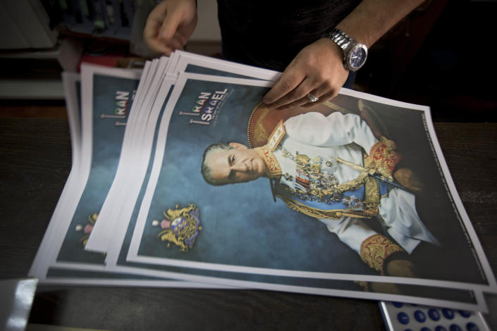 In this photograph made on Sunday, Feb. 12, 2012, Kamal Penhasi, the Iranian-born editor of Shahyad, the only Persian-language magazine published in Israel, works on posters showing the former Iranian Shah Reza Pahlavi at his print house In the israeli town of Holon. There are an estimated 250,000 Jews of Iranian descent in Israel. (AP Photo/Oded Balilty)