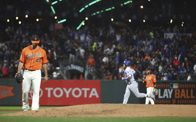 San Francisco Giants' Madison Bumgarner, left, waits for Los Angeles Dodgers' Justin Turner, right, to run the bases after hitting a two-run home run during the fifth inning of a baseball game Friday, Sept. 28, 2018, in San Francisco. (AP Photo/Ben Margot)