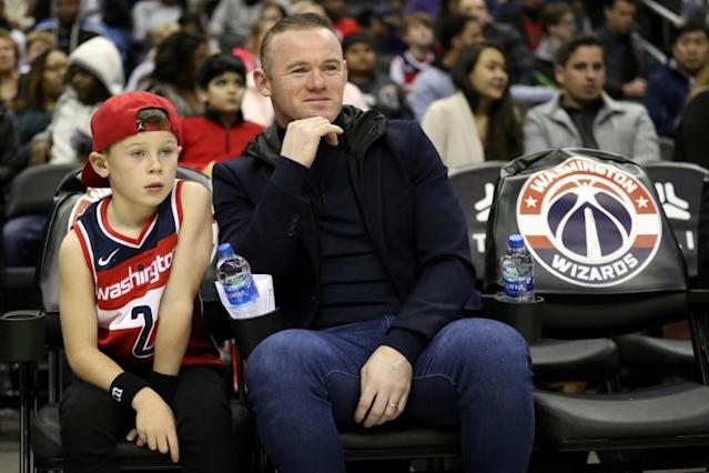 DC United striker Wayne Rooney, in center with his son watching an NBA game, said Tuesday he has not made any plans for a return to England (AFP Photo/Patrick Smith)
