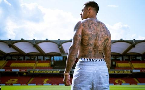 "Andre Gray's new tattoo took nine eight-hour sessions to have inked on to his back, but has been three years in the making. Even the briefest of glances at his back tells you that his tattoo is no ordinary Premier League footballer's fashion accessory. Muhammad Ali and Bob Marley sit alongside images of Rosa Parks, Marcus Garvey, the Black Panthers and Tommie Smith and John Carlos, who famously protested at the Mexico Olympics. All are inspirations for Watford's record signing after he first started reading up on the African-American civil rights movement.  Unsurprisingly, the tattoo provoked a huge and varied response after Gray posted a picture of it on Twitter last week, but the 26 year-old is clearly extremely well versed in the pictures and slogans that he has chosen to have permanently imprinted.  Annotated: Andre Gray's tattoos ""The civil rights movement is something I've looked into a lot,"" said Gray. ""When I was about 23, I started reading up on it all and watching TV programmes. You find you read about one person and then you find there is a documentary you can watch about them and then it usually leads on to something else.""  Asked to pick out one of the figures who has become of particular interest to him, Gray replied: ""Marcus Garvey. He was the first person to really start trying to fight back and fight for equal rights. Most interesting for me, he created a ship, which is on the tattoo as well, to take African Americans back to Africa from other countries.  ""He was the one a lot of other famous civil rights activists looked up to and he had Jamaican heritage as well, like me, so it was really interesting for me. Then you start watching videos on YouTube and all these other people pop up and you learn more and more.""  Andre Gray has had his back inked with icon figures of the African-American civil rights movement Credit: GEOFF PUGH Other than reading up and watching videos on civil rights, Gray also took time out during his summer holiday to try to educate himself further before making an £18.5 million move from Burnley to Watford.  ""I went to Zanzibar on holiday and there was a lot there about civil rights and there was a museum, where there are old slave chambers,"" he said. ""It was horrible to go to and they've still got the chains there. It opens your eyes a lot. To go to Africa and see some of those things was pretty difficult, but it makes you think.""  Thinking and learning are two things Gray has done a lot of during his rise from non-League football and gang culture that he is sure would have resulted in him going to prison if he had not moved away from Wolverhampton.  He was stabbed in the face during a night out in 2011 and last season served a ban after homophobic tweets he posted in 2012 came to light just after the striker had scored his first Premier League goal against Liverpool.  ""I had changed a long time before the tweets were exposed,"" said Gray. ""I couldn't even imagine I would have written them because they don't represent the person I am now. I didn't know they were there, I thought they were fake.""  Credit: GEOFF PUGH Gray, who joined Luton Town from Hinckley United in March 2012, added: ""The best thing that happened to me was going to Luton and being able to get away from it all and not be in the position to be dragged back into anything in terms of getting into trouble with the police.  ""I try not to think about where I would be now if I had stayed in Wolverhampton. Jail. That's the way I would have seen it. It was just part and parcel of where I grew up and the lifestyle I was in. I've got one friend that hasn't been to jail - it was just normal and it's not seen as a massive thing. It's part of life where I'm from.""  Gray has been the recipient of racist abuse during his career and admitted that his first instinct used to be to fight. But reading the stories of Smith and Carlos, who silently protested while collecting their gold and bronze medals in the Mexico Olympics, has taught him there are other ways to react. ""Yeah 100 per cent and that is why the picture of the Olympians was a big piece that I really wanted to get on the tattoo,"" said Gray. ""There was also the Australian guy [Peter Norman] who stood with them and supported them, and that was a massive moment. He got a lot of stick and hate for it, but it showed somebody in the limelight could stand up and help change things. It's something you have to do when you are in that position.""  Andre Gray in action for Watford Credit: GETTY IMAGES Gray is still waiting for his first Watford goal, but the team has made a superb start to the season and are unbeaten in the Premier League ahead of Saturday's game against Manchester City at Vicarage Road.  Squaring up to Sergio Aguero is not something Gray could have envisaged five years ago, when the Argentine scored the goal that clinched City's first top-flight title for 44 years.  ""I watched it in a pub with my friends in Wolverhampton,"" said Gray. ""I think I had been at Luton in the Conference and the season had already finished. I'd have never believed you if you'd have told me I would be sharing a pitch with Aguero, that's crazy.  ""It's hard to see yourself in the Premier League when you are in the Conference because the jump is so high. When I was there nobody had done it. Jamie Vardy got his move to Leicester, but that was in the Championship so the Premier League seemed like a very long way away.  ""The boys at Luton used to tell me I would get a move and people said I'd play in the Premier League, but I found it laughable. I just thought 'how can you say that?' You know yourself how good you are, but you are playing in non-League and it's hard to believe."""