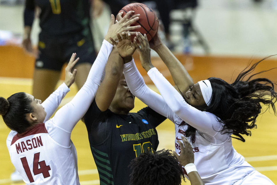 Wright State forward Shamarre Hale, center, battles for the rebound with Arkansas guard Jailyn Mason (14) and forward Erynn Barnum during the first half of a college basketball game in the first round of the women's NCAA tournament at the Frank Erwin Center in Austin, Texas, Monday, March 22, 2021. (AP Photo/Stephen Spillman)