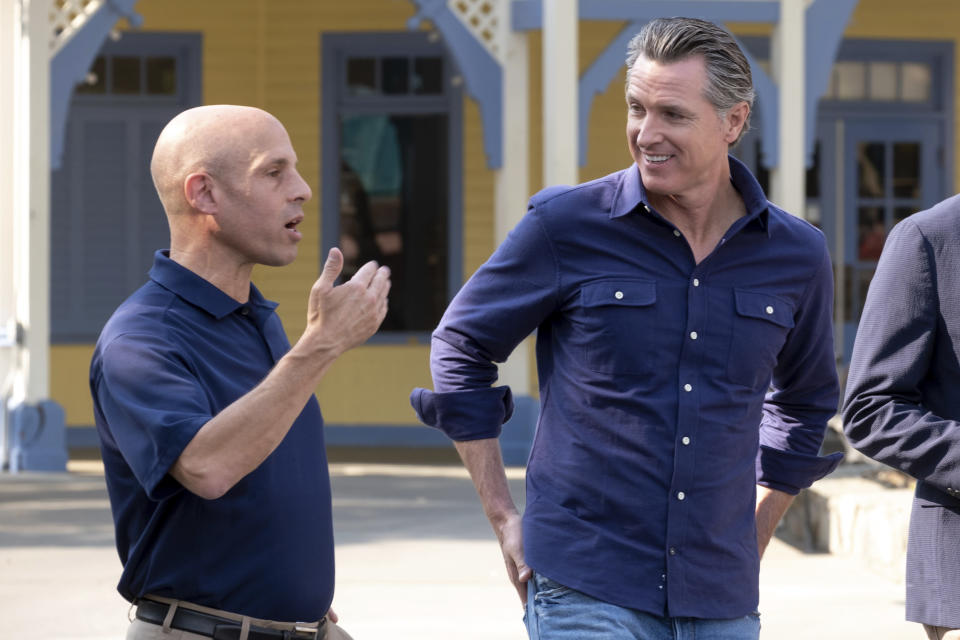 Michael Spanos, President of Six Flags, left, talks with California Gov. Gavin Newsom as they tour Six Flags Magic Mountain in Santa Clarita, Calif., Wednesday, June 16, 2021. Newsom continued his tour of the state after lifting most COVID-19 restrictions Tuesday. (David Crane/The Orange County Register via AP)
