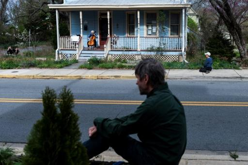 People watch cellist Jodi Beder perform a daily concert on her front porch in Mount Rainier, Maryland near Washington, DC