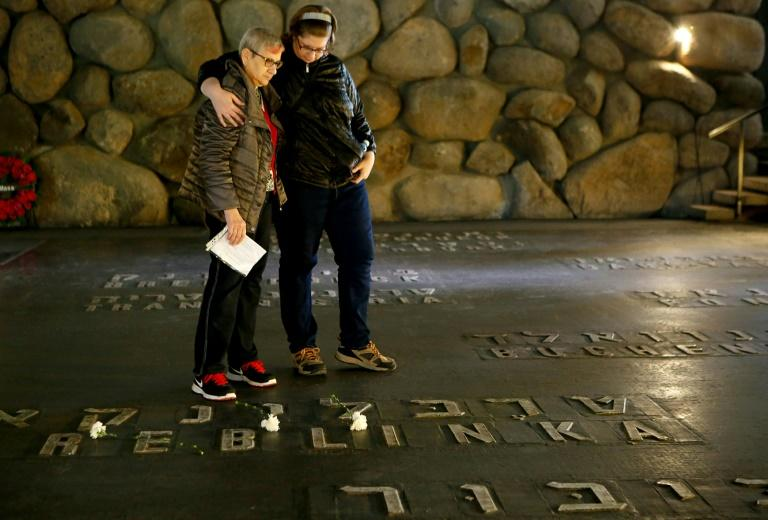 Israeli relatives of a Holocaust survivor stand at the Hall of Remembrance, where the names of major death and concentration camps are written, at the Yad Vashem Holocaust Memorial in Jerusalem (AFP Photo/GIL COHEN-MAGEN)