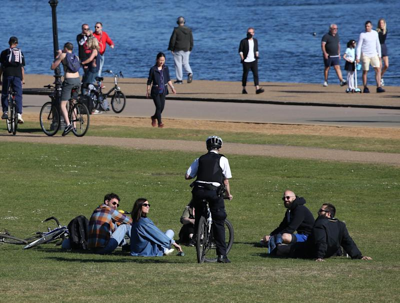 A police officer speaks to people relaxing by the Serpentine in Hyde Park, London, as the UK continues in lockdown to help curb the spread of the coronavirus. (Photo by Jonathan Brady/PA Images via Getty Images)