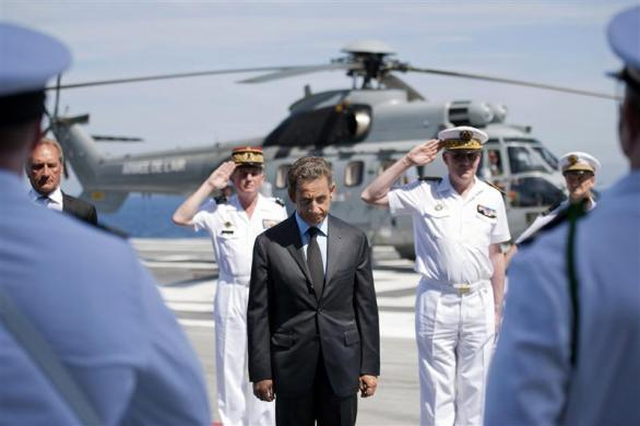 France's President Nicolas Sarkozy reviews the troops on the deck of the aircraft carrier Charles de Gaulle, August 12, 2011 as it returns to the port of Toulon for maintenance after participating in the NATO-led mission against Libya.