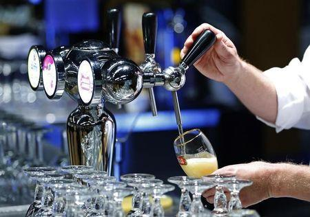 A waiter serves a glass of beer ahead of an Anheuser-Busch InBev shareholders meeting in Brussels April 30, 2014. REUTERS/Yves Herman