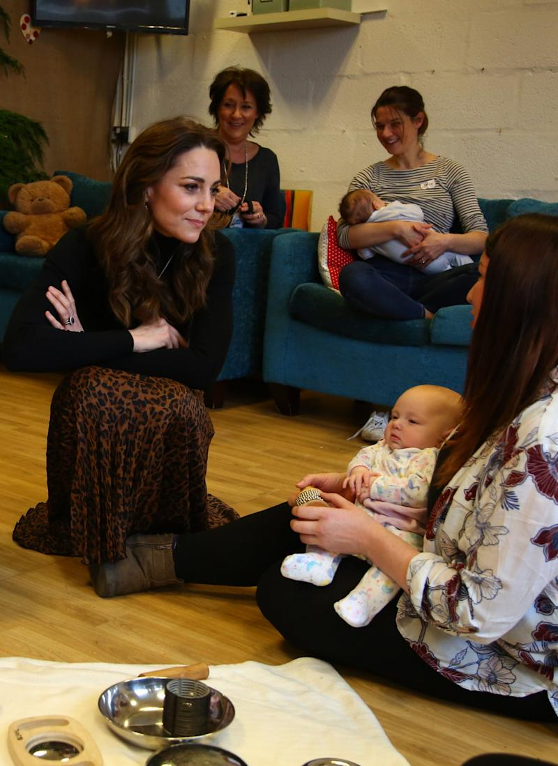 The Duchess of Cambridge chats with mothers and their children during a visit to Ely and Careau Childrens Centre (Getty Images)