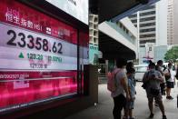 People wearing face mask walk past a bank's electronic board showing the Hong Kong share index in Hong Kong Monday, Sept. 28, 2020. Asian shares were mostly higher in muted trading Monday, ahead of the first U.S. presidential debate and a national holiday in China later in the week.(AP Photo/Vincent Yu)