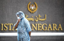 Police stand guard in the rain at the main entrance of the National Palace in Kuala Lumpur, Malaysia, Friday, Aug. 20, 2021. Malaysian state royals are meeting Friday at the national palace to discuss the appointment of a new prime minister, with the likely choice stirring public anger and warnings of more political instability. (AP Photo/FL Wong)