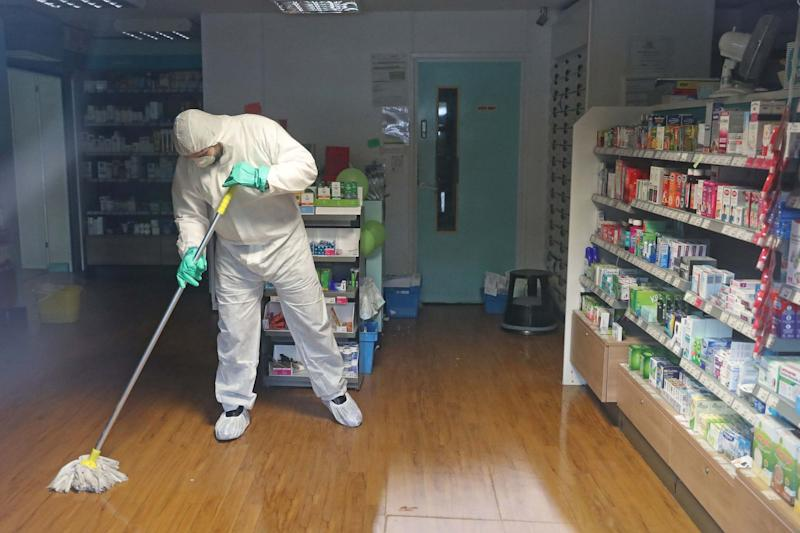 A man in protective clothing cleaning the County Oak Medical Centre GP practice (PA)